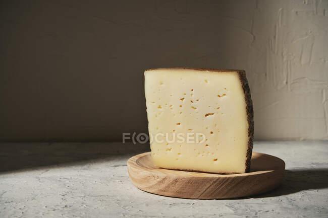Треугольный кусок вкусного свежего твердого сыра, выложенный на деревянную доску на столе в легкой студии — стоковое фото