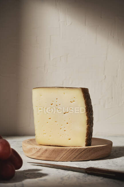 Triangle piece of delicious fresh hard cheese placed on wooden board near grapes on table in light studio — Stock Photo