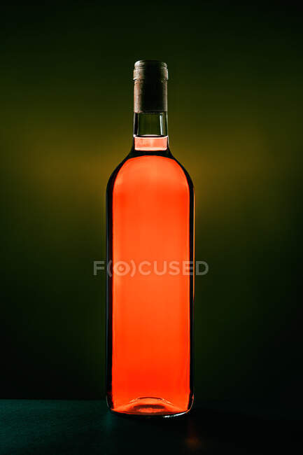 Garrafa de vinho tinto de mesa aromático colocada em estúdio sobre fundo escuro — Fotografia de Stock
