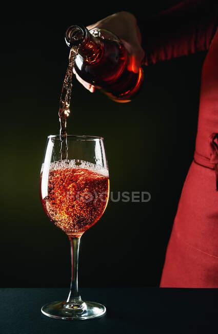 Crop unrecognizable barman in red apron pouring semi sweet fine red wine into wineglass in dark studio — Stock Photo