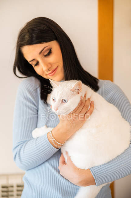 Content young female embracing and stroking adorable fluffy cat with white fur at home — Stock Photo