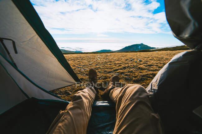 Незнайомий чоловік - мандрівник у звичайному одязі, який лежить у кемпінгу і милується мальовничим гірським краєвидом у сонячний день. — стокове фото