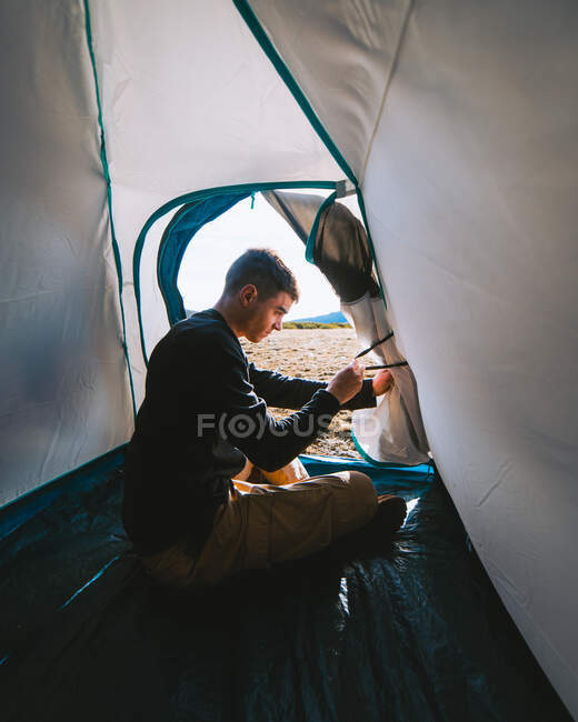 Side view of concentrated young male camper in casual outfit opening tent door while recreating during hiking trip on sunny day in mountains — Stock Photo