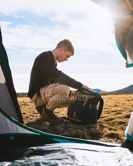 Young stylish male camper in casual outfit checking backpack inside of tent during hiking trip in mountainous valley in sunlight — Stock Photo