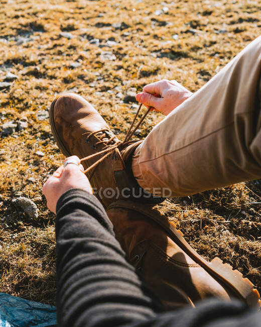 From above of crop anonymous male hiker in stylish outfit tying laces of boots while sitting on grassy ground on sunny day — Stock Photo