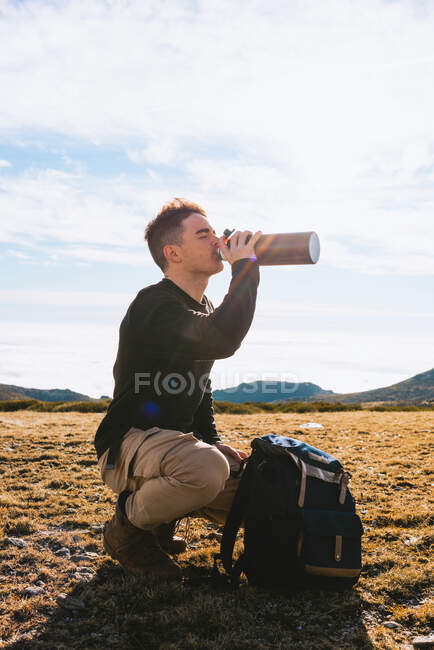 Side view of young stylish male traveler in casual outfit sitting on haunches near backpack and drinking hot beverage from thermos during hiking trip in mountainous terrain — Stock Photo