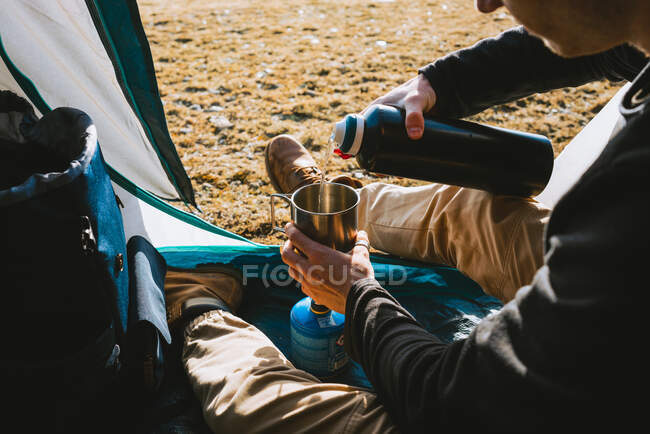 From above of crop unrecognizable young male camper in warm clothes poring hot drink from thermos into mug while resting in tent on sunny day — Stock Photo