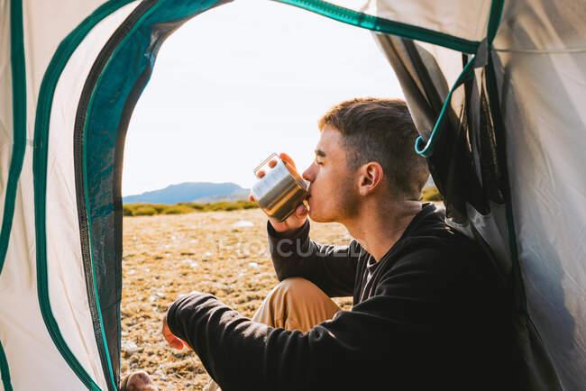 Уверенный молодой модный турист в теплой одежде, пьющий кружку горячего напитка во время отдыха в палатке в солнечный день — стоковое фото