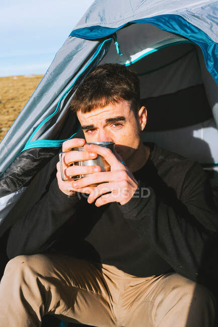 Уверенный молодой модный турист в теплой одежде, пьющий кружку горячего напитка и смотрящий в камеру во время отдыха в палатке в солнечный день — стоковое фото