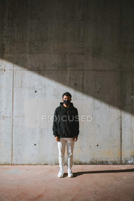 Unrecognizable young male in hoodie and mask standing on street near concrete wall and covering face with hand from bright sunlight — Stock Photo