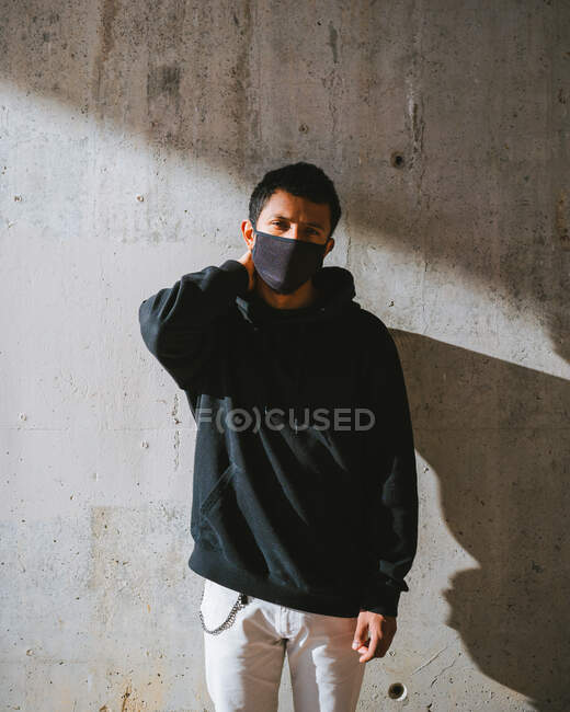 Trendy guy in face mask adjusting hoodie and looking away while standing on street near shabby wall on sunny day — Stock Photo