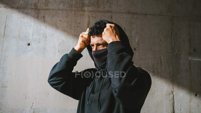 Anonymous trendy guy in face mask adjusting hoodie and looking away while standing on street near shabby wall on sunny day — Stock Photo