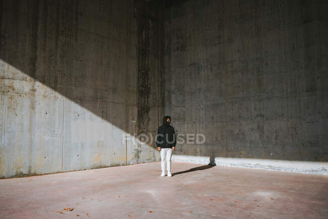 Full body of unrecognizable male in stylish hoodie and protective mask standing in abandoned building near shabby concrete walls and looking away — Stock Photo
