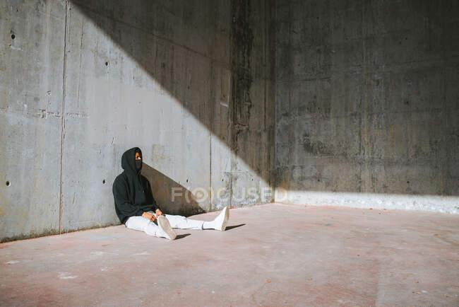 Неузнаваемый молодой мужчина в толстовке и маске сидит на улице возле бетонной стены — стоковое фото