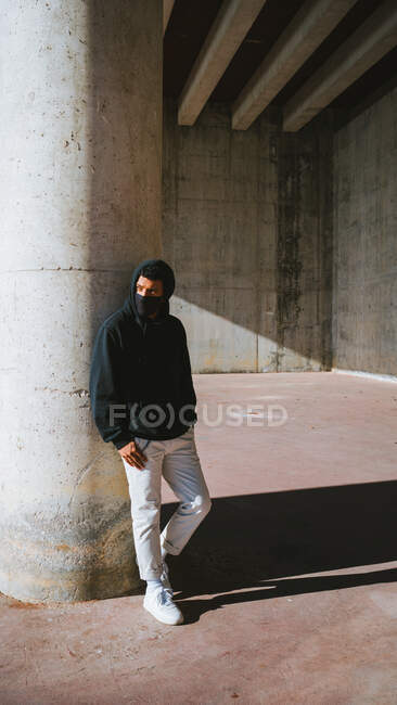 Trendy guy in face mask looking away while standing on street near shabby wall on sunny day — Stock Photo