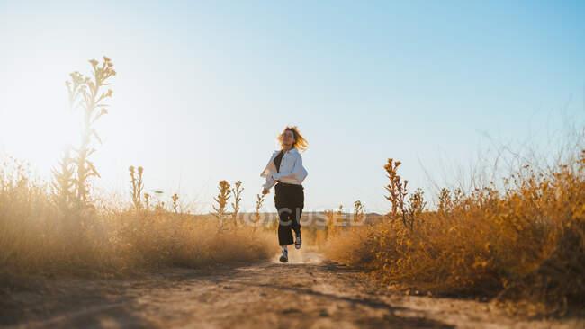 Вид спереди на модную молодую туристку с светлыми волосами в повседневной одежде и очках, бегущую по сельской дороге среди сухих растений в сельской местности — стоковое фото