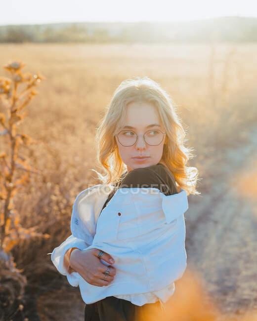 Вид сбоку уверенной в себе молодой женщины в повседневной одежде и очках, стоящей в закусочной и отводящей взгляд в сторону, расслабляясь за городом на закате — стоковое фото