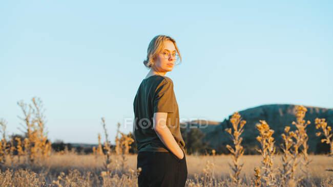 Vista lateral de la joven viajera confiada en ropa casual y anteojos de pie en el prado y mirando a la cámara mientras se relaja en el campo al atardecer - foto de stock