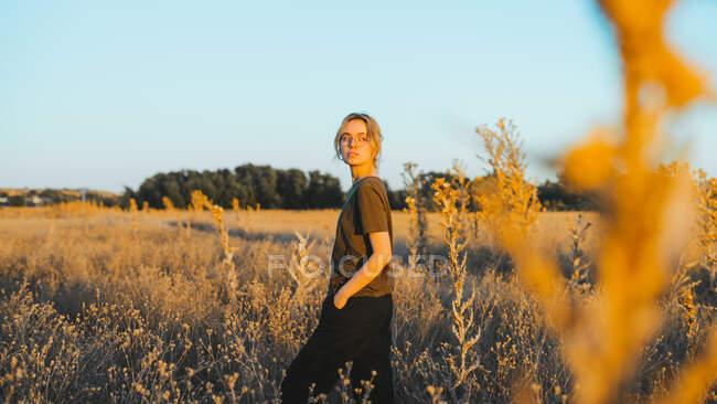Vue latérale de la jeune voyageuse confiante en vêtements décontractés et lunettes debout dans la prairie et regardant loin tout en se relaxant à la campagne au coucher du soleil — Photo de stock