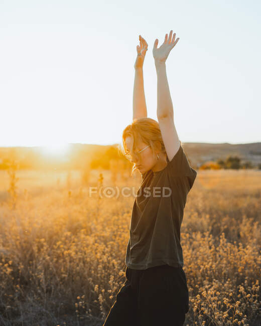 Side view of young female in casual clothes enjoying summer day while standing in dry field with raised arms at sunset in countryside — Stock Photo