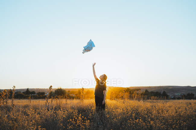 Неузнаваемые молодые туристки в повседневной одежде бросают куртку, стоя на цветущем лугу в холмистой сельской местности на закате — стоковое фото