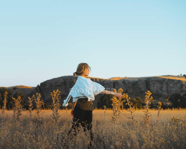 Vista lateral de la joven con el pelo rubio en ropa elegante caminando en medio de la hierba en el campo rural cerca de las colinas contra el cielo azul sin nubes al atardecer - foto de stock