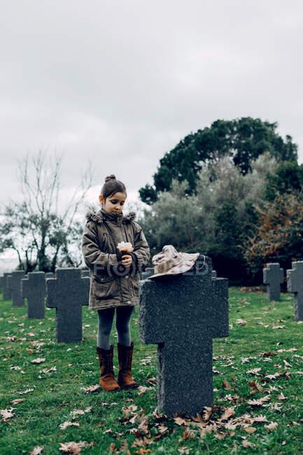 Niño pequeño llorando la muerte de soldado luchando en la guerra en el cementerio - foto de stock