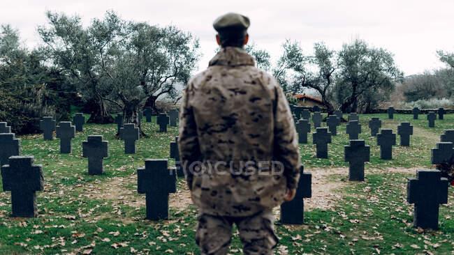 Vista posterior soldado anónimo con traje de camuflaje de pie en el vasto cementerio militar en los primeros días de otoño - foto de stock