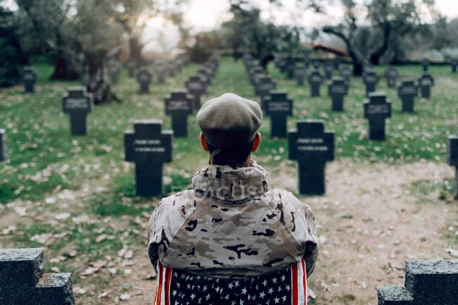 Vista trasera de soldado en uniforme sentado en silla con bandera americana mientras lloraba la muerte de guerreros en el cementerio - foto de stock