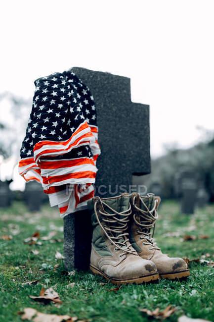 Государственный американский флаг и армейский флаг помещены на надгробии на военном кладбище в ранний осенний день — стоковое фото