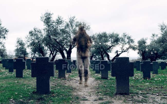 Anonymer Soldat in Tarnkleidung mit Kriegerrucksack läuft auf geräumigem Soldatenfriedhof — Stockfoto