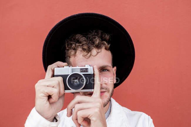 Впевнений молодий чоловік з кучерявим волоссям в модному одязі і капелюсі посміхається, фотографуючи ретро-камеру на червоному фоні. — стокове фото