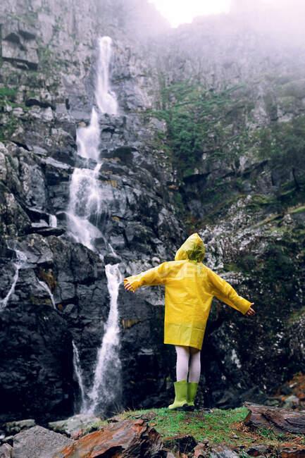 Vista posteriore di adolescente donna irriconoscibile in impermeabile luminoso con braccia sollevate in piedi contro cascata con flusso d'acqua veloce sul monte — Foto stock