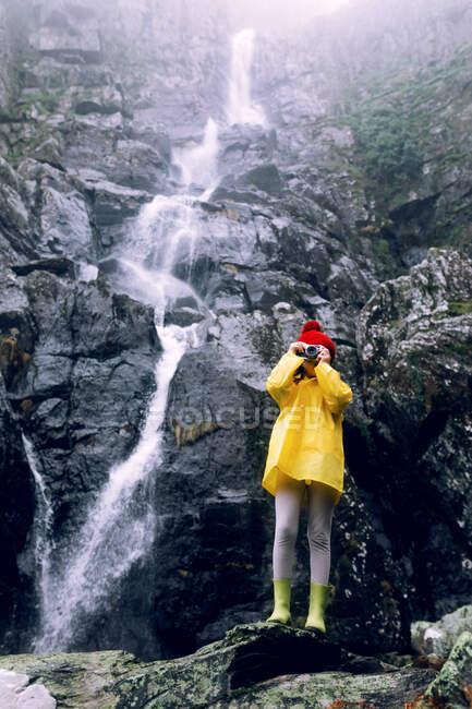 Adolescente anonimo in impermeabile scattare foto sulla macchina fotografica contro il supporto ruvido con schiumosa cascata alla luce del giorno — Foto stock