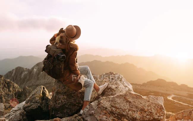 Vue latérale d'un randonneur méconnaissable assis sur la pierre et observant des paysages étonnants de la vallée des hautes terres par une journée ensoleillée — Photo de stock
