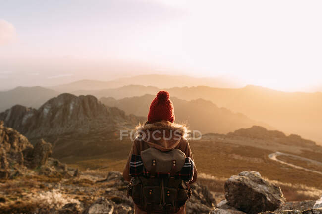 Back view of unrecognizable hiker standing on stone and observing amazing scenery of highlands valley on sunny day — Stock Photo
