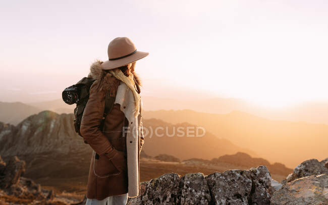 Side view of unrecognizable hiker standing on stone and observing amazing scenery of highlands valley on sunny day — Stock Photo