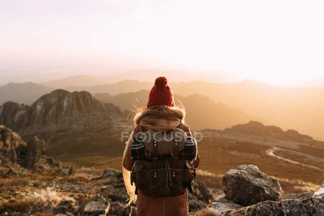 Повернення до непізнаного мандрівника, що стоїть на камені і бачить дивовижні краєвиди високогірної долини в сонячний день. — стокове фото