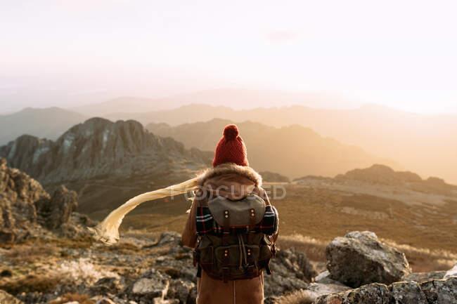 Vista trasera de un excursionista irreconocible de pie sobre piedra y observando un paisaje increíble del valle de las tierras altas en un día soleado - foto de stock