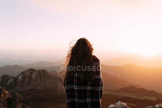 Vista trasera de excursionista irreconocible en manta de pie sobre piedra y observando paisajes increíbles del valle de las tierras altas en un día soleado - foto de stock