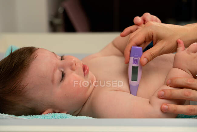 Madre cariñosa del cultivo que mide la temperatura del bebé lindo y coloca el termómetro en la axila del bebé cuidadosamente - foto de stock