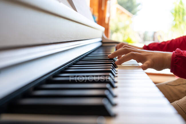 Cropped anonymous child playing piano while reading notes and rehearsing song at home — Stock Photo