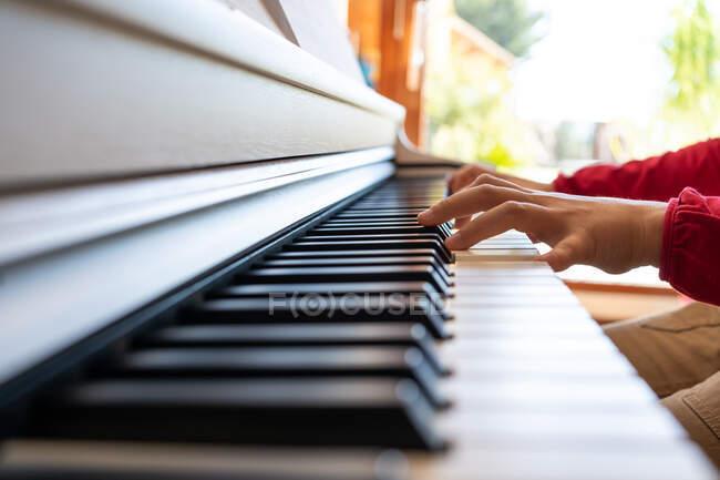 Anonymisiertes Kind spielt Klavier, während es zu Hause Noten liest und Lieder probt — Stockfoto