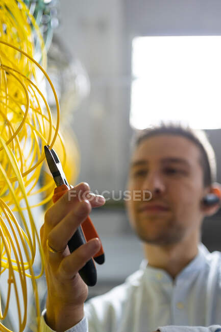 From below blurred male technician with wire cutters working with electronic system of server room — Stock Photo