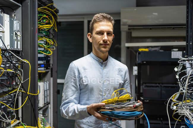 Hombre sonriente con auriculares inalámbricos de pie con cables en la sala de servidores de red para proporcionar Internet y comunicación - foto de stock
