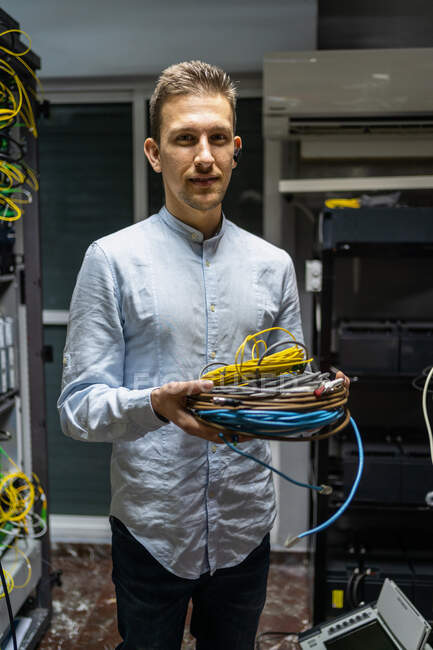 Smiling man in wireless headset standing with cables in network server room for providing Internet and communication — Stock Photo