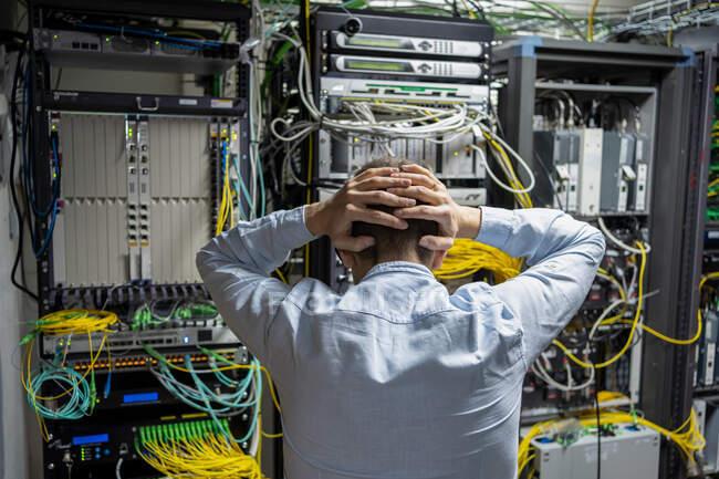 Vista posterior de un técnico masculino irreconocible agarrando el cabezal mientras tiene problemas en el centro de datos con bastidores de servidor - foto de stock