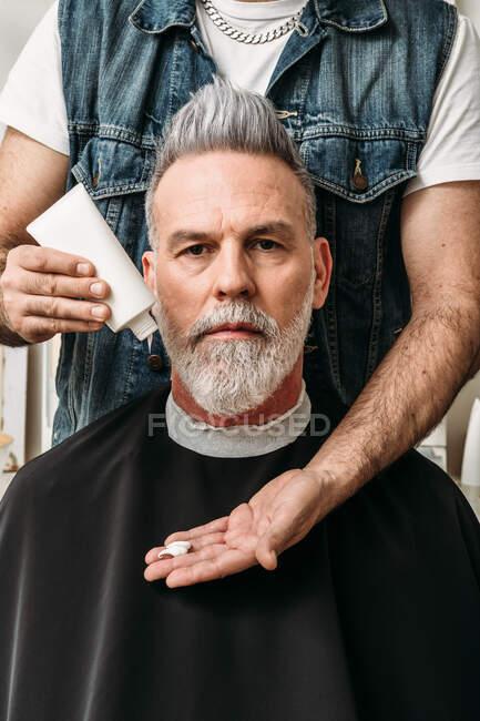 Анонимный самец парикмахера, стоящий позади серьезного бородатого клиента среднего возраста и готовящийся к прическе кремом — стоковое фото
