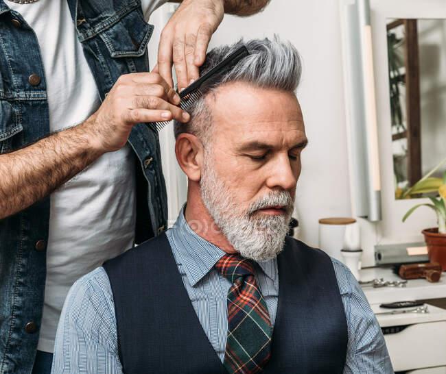Анонимный парикмахер-стригущий волосы элегантного бородатого мужчины среднего возраста, сидящего на стуле и смотрящего в сторону в современной студии — стоковое фото