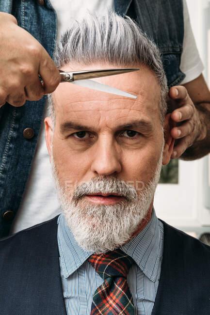 Безликий парикмахер стрижет седые волосы элегантного клиента среднего возраста с бородой в костюме и галстуке — стоковое фото